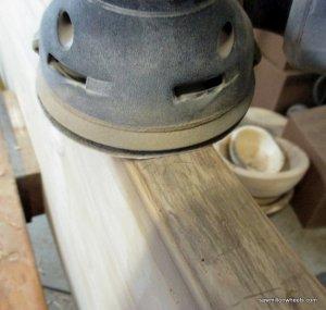 Sanding live edge lumber.